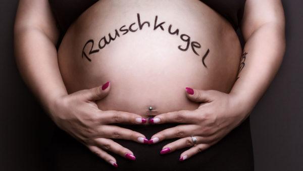 Fotograf Schwarzwald Babybauch Frau hält ihren Bauch mit der Aufschrift Rauschkugel