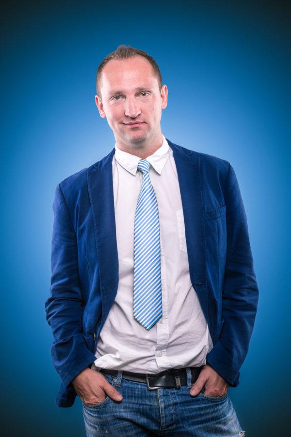 Fotograf Schwarzwald Business Mann mit Krawatte blauem Sakko vor blauem Hintergrund