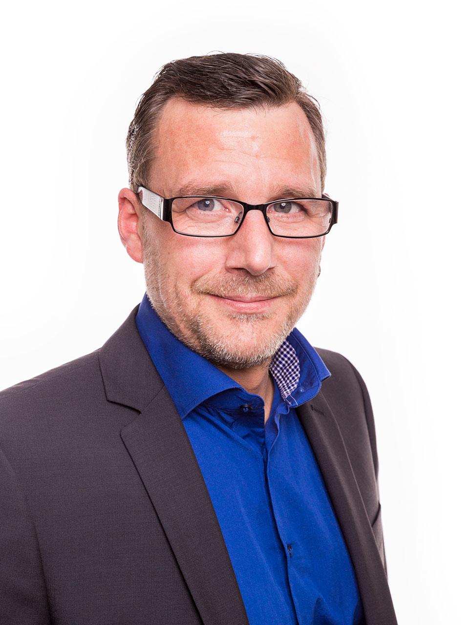 Fotograf Schwarzwald Business Mann mit Brille Sakko und blauem Hemd vor weißem Hintergrund
